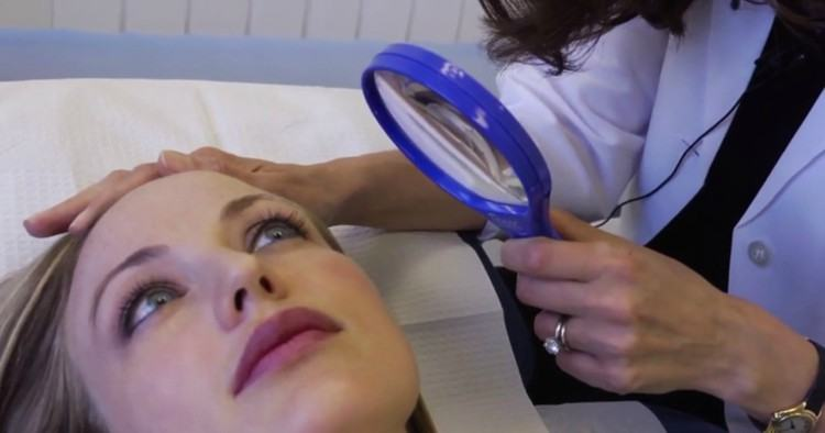 Image of woman having her face examined.