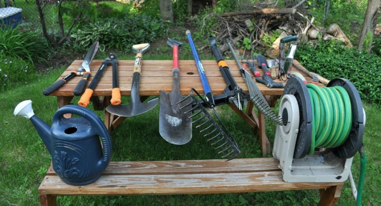 Gardening tools lined up on picnic table