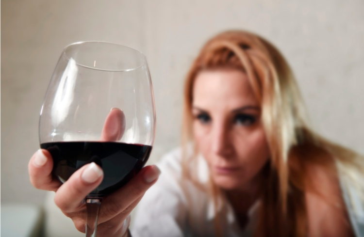 Image of woman holding glass of wine.