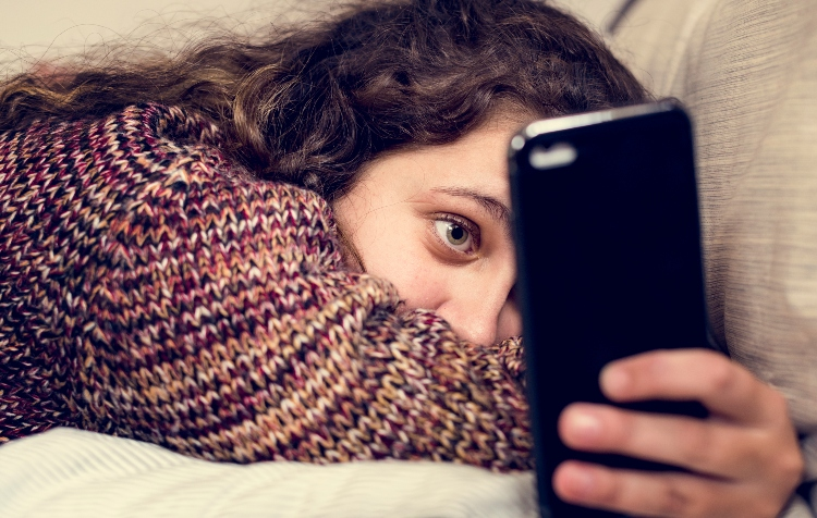 Image of Teenage girl using a smartphone on a bed social media and addiction concept