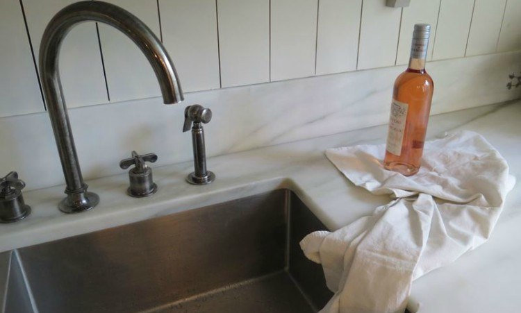 wine bottle sitting on a towel on top of a sink