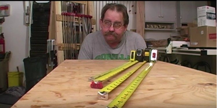 Tom Hintz poses with several tape measurers