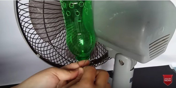 person attaching a water bottle to a fan