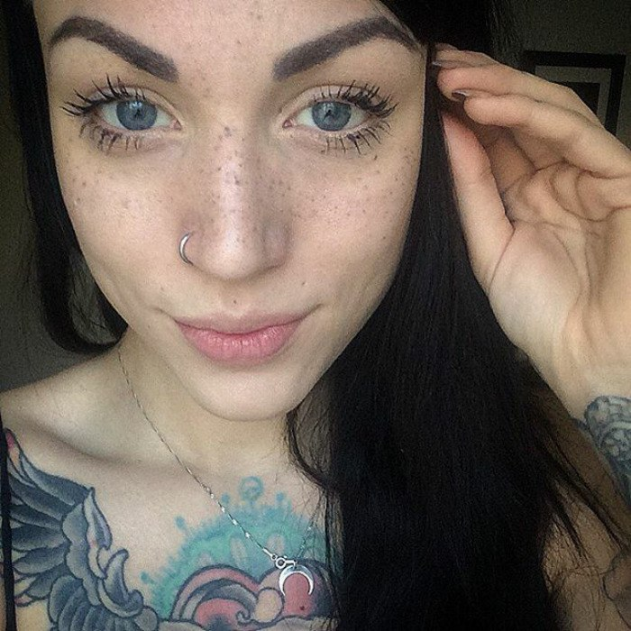 Young woman with tattooed freckles.