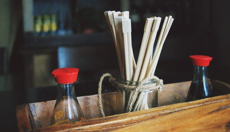 soy sauce bottles in basket with chopsticks