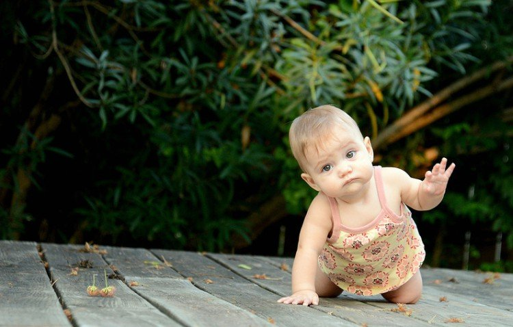 Baby girl crawling on deck.