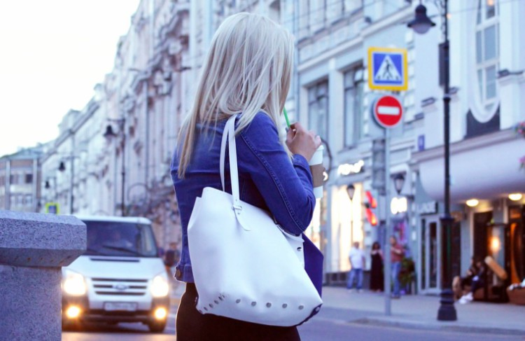 Image of woman with purse walking outside.