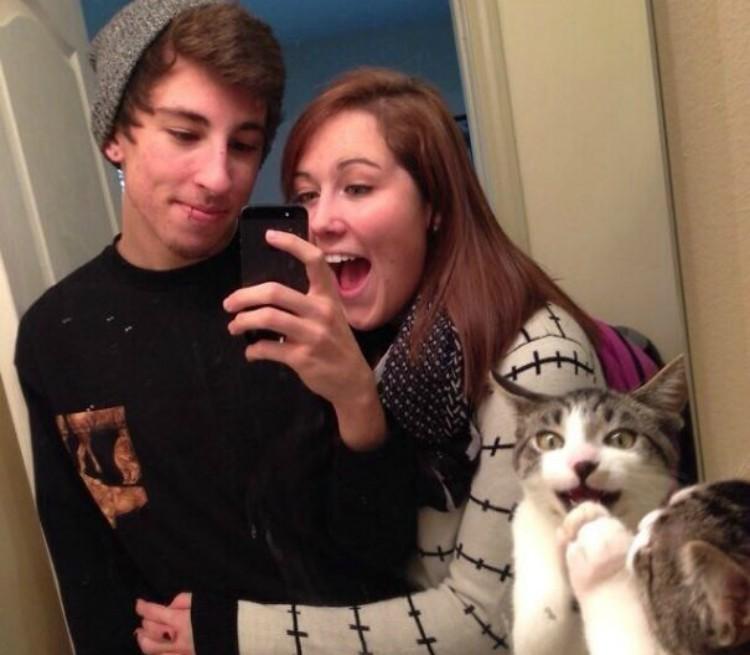 Boy and girl taking mirror selfie.