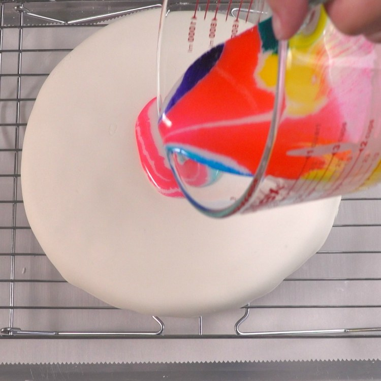 Beginning to pour tie dye glaze on fondant-covered cake