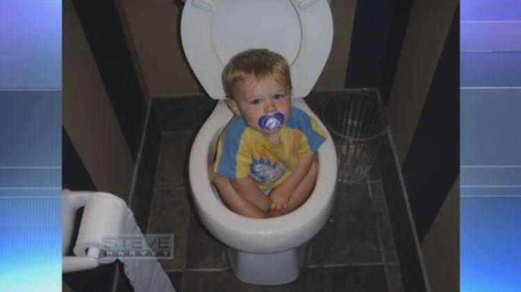 Toddler sitting inside toilet bowl