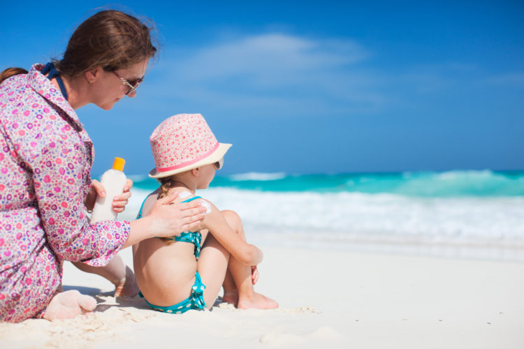 Image of Mother applying sunblock cream on her daughters shoulder