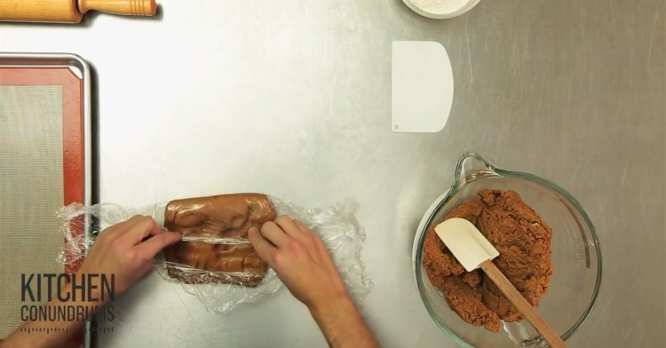 Using plastic wrap to mold cookie dough.