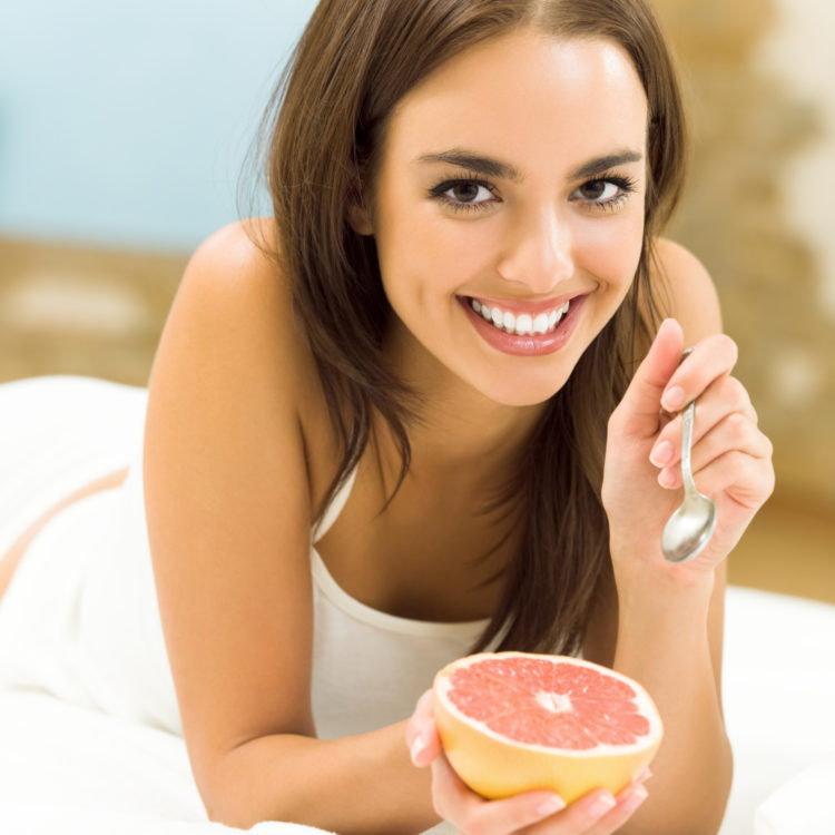 Image of young woman eating grapefruit at home