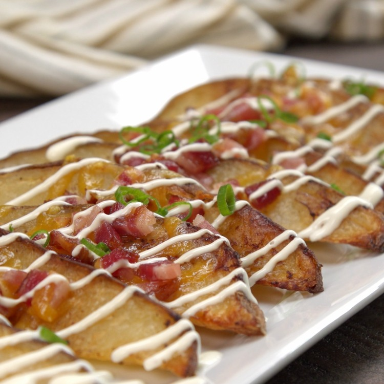 Baked potato wedges loaded with bacon, cheese and green onions