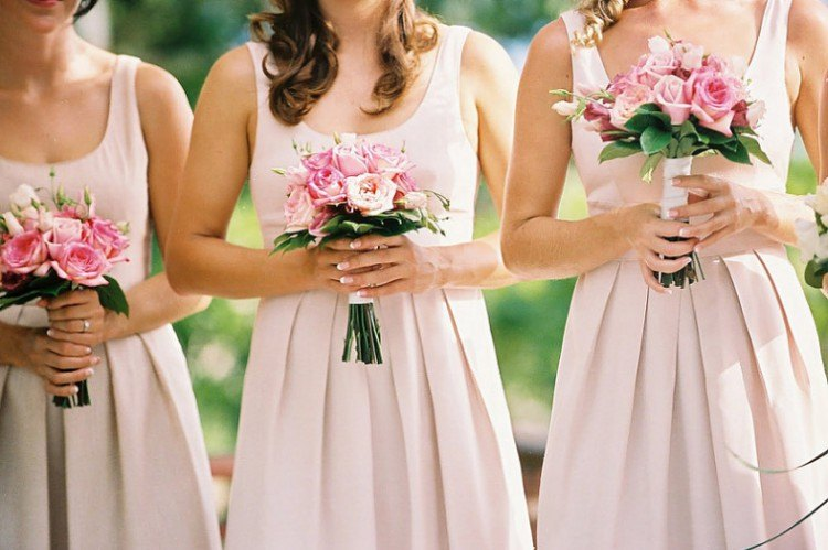 Bridesmaids all wearing pink dresses.