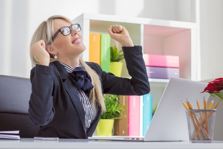 Happy young business woman enjoying success at work