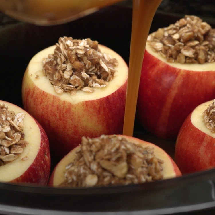 Pouring caramel sauce into slow cooker between apples