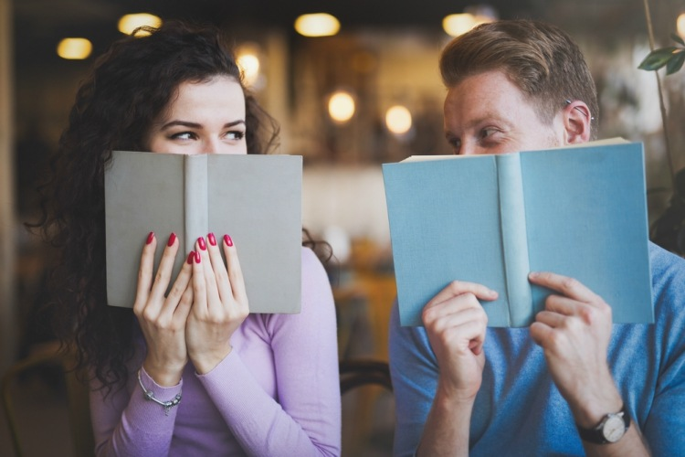 Introverted couple flirting behind books