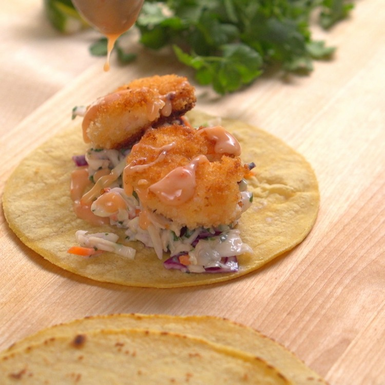 Dripping sweet chili sauce onto shrimp taco