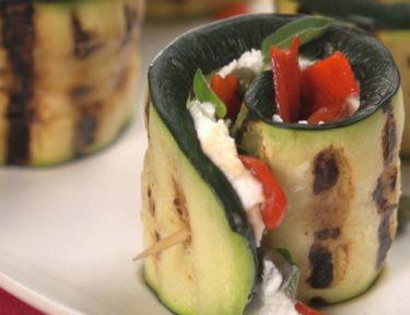 Close-up of grilled zucchini rolls with goat cheese, capers and peppers
