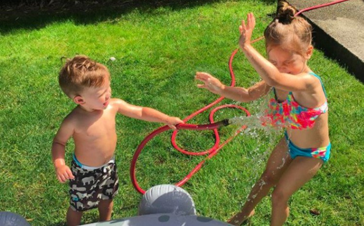 brother sprays sister with hose