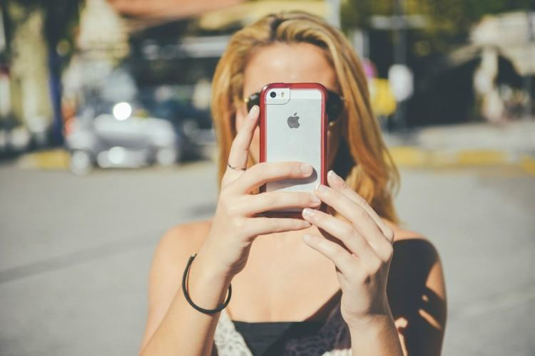 Image of woman taking a smartphone pic.