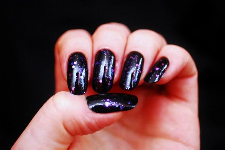 Fingernails painted with purple sparkle polish