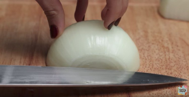 Dicing onion with chef knife.