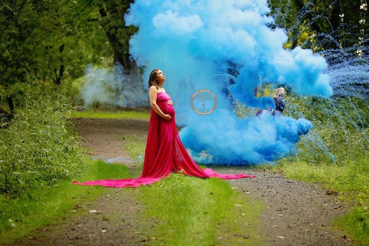 Image of pregnant mom with rainbow baby blue smoke.