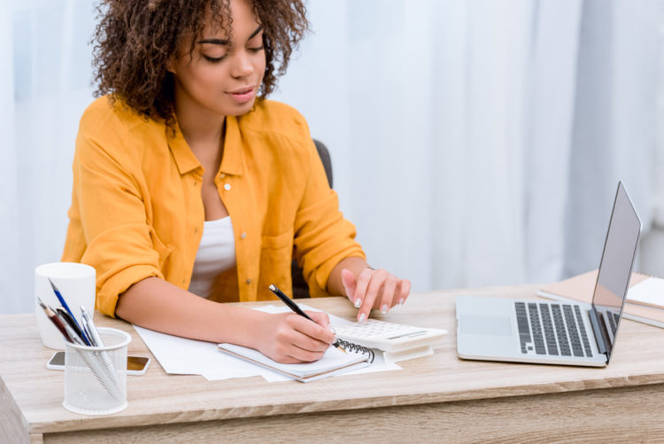 Image of woman writing at desk