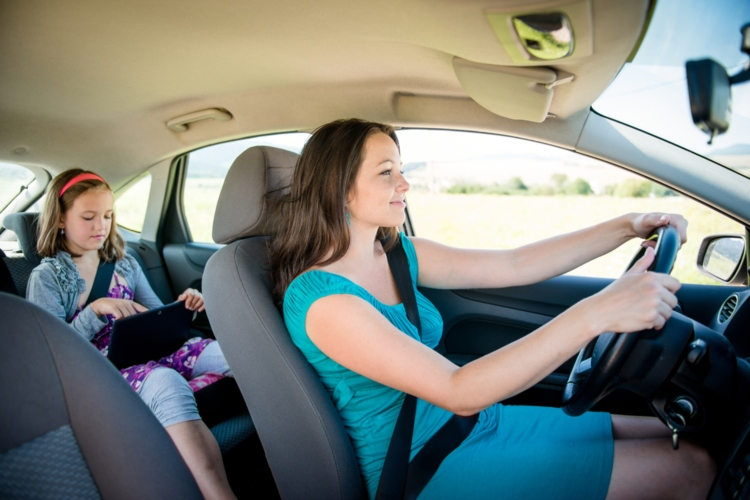 Mother driving car and child sitting on back seat and playing with tablet