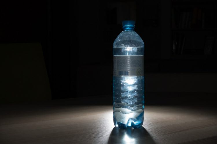 glowing blue water bottle on black background