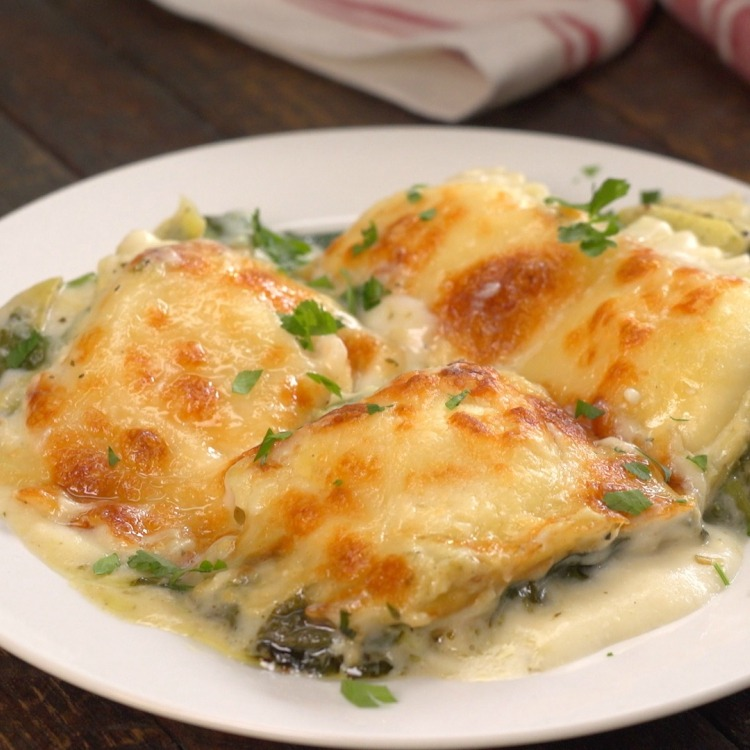 Ravioli baked with spinach and artichoke sauce