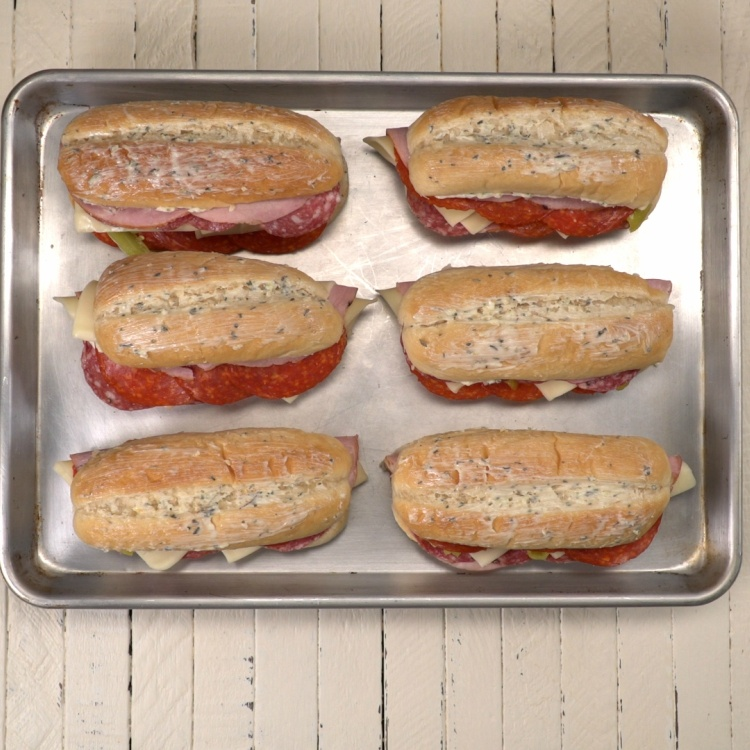 Italian sandwiches spread with garlic herb butter before baking