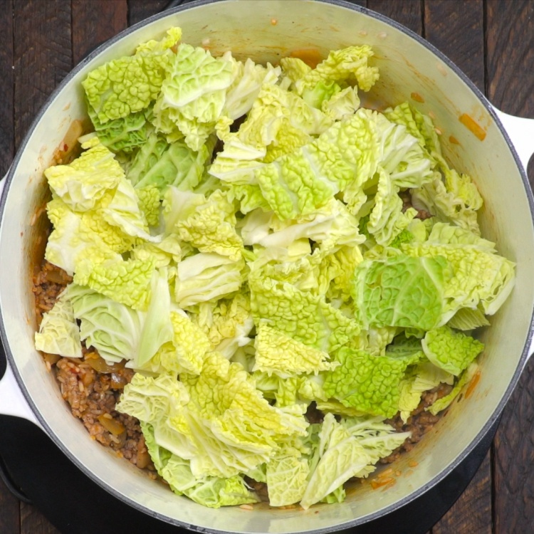 Adding cabbage leaves to cabbage roll soup