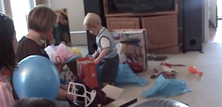 Little boy stares at his birthday present in shock.