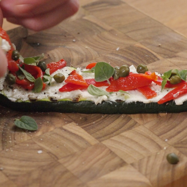 Rolling grilled zucchini slice layered with goat cheese, capers and peppers
