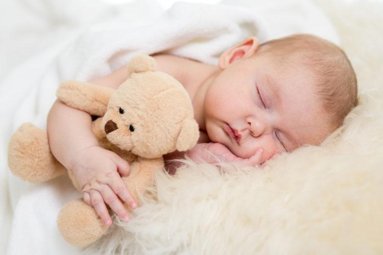 Newborn baby boy sleeping on a fur rug.