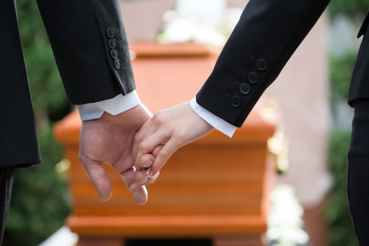 Image of people holding hands at funeral.