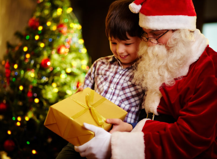 Image of boy and Santa Claus holding giftbox and looking at it