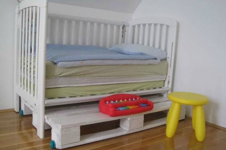 Converted toddler bed made from pallets with crib sides