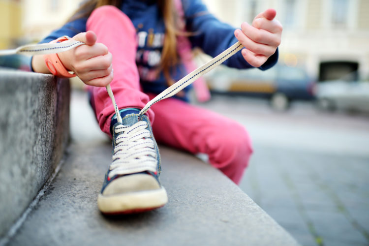 Image of girl learning to tie shoelaces outdoors on summer day