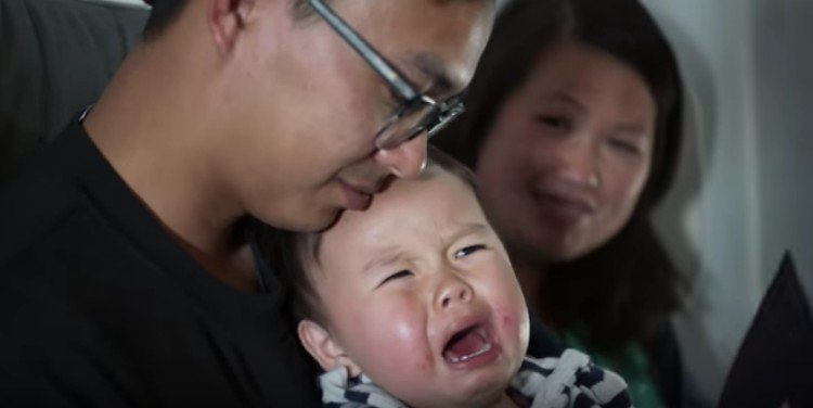 baby screaming next to parents on airplane