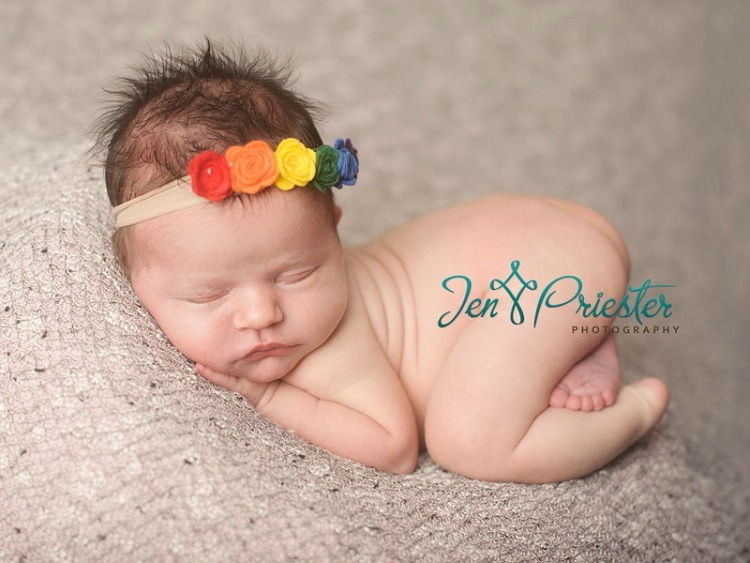 Rainbow baby Charlotte sleeps curled up with rainbow headband