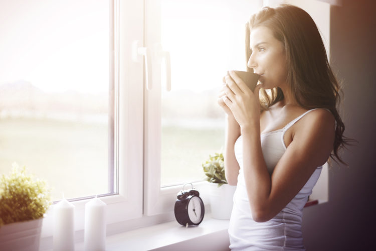 Image of woman drinking coffee by a window