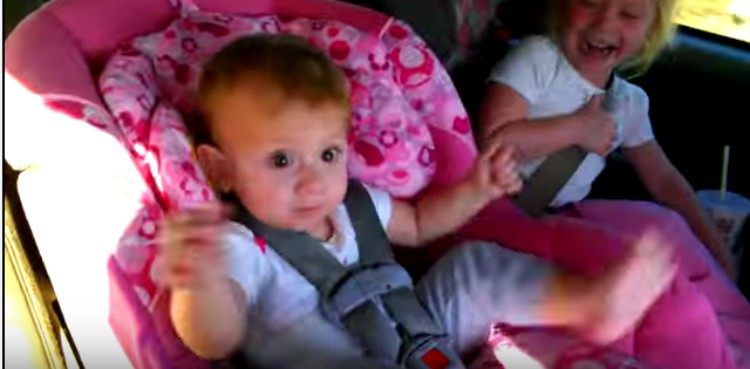 baby Amaya dances in car seat while sister watches