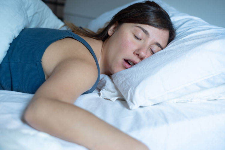 Image of one tired woman snoring in bed