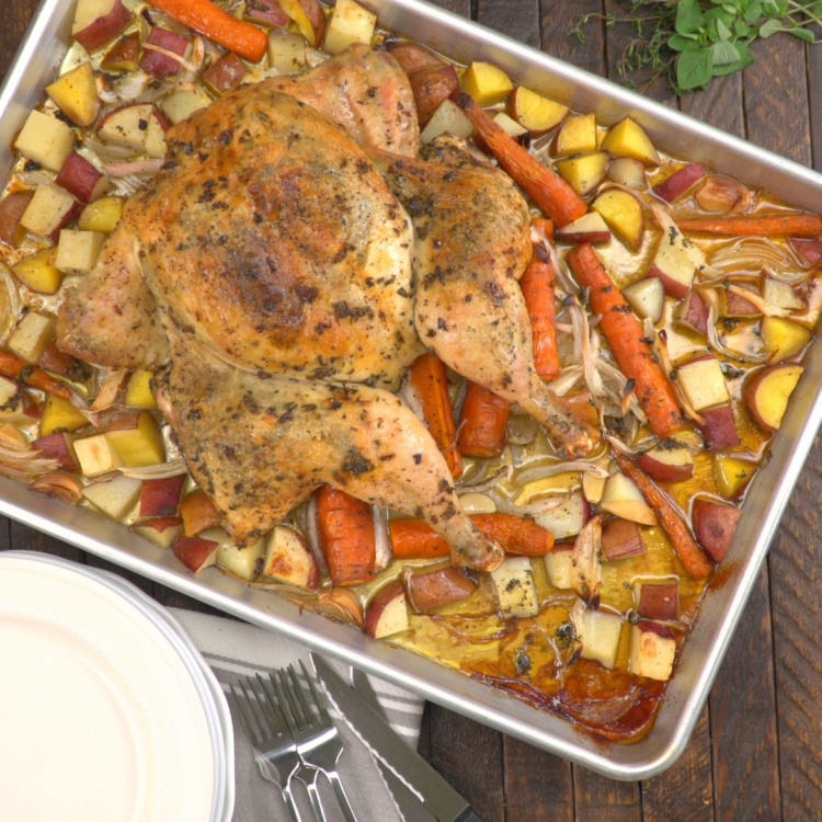 Overhead one-pan garlic herb spatchcock chicken and vegetables