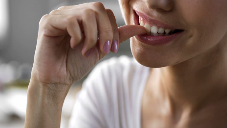 Image of woman biting nails.
