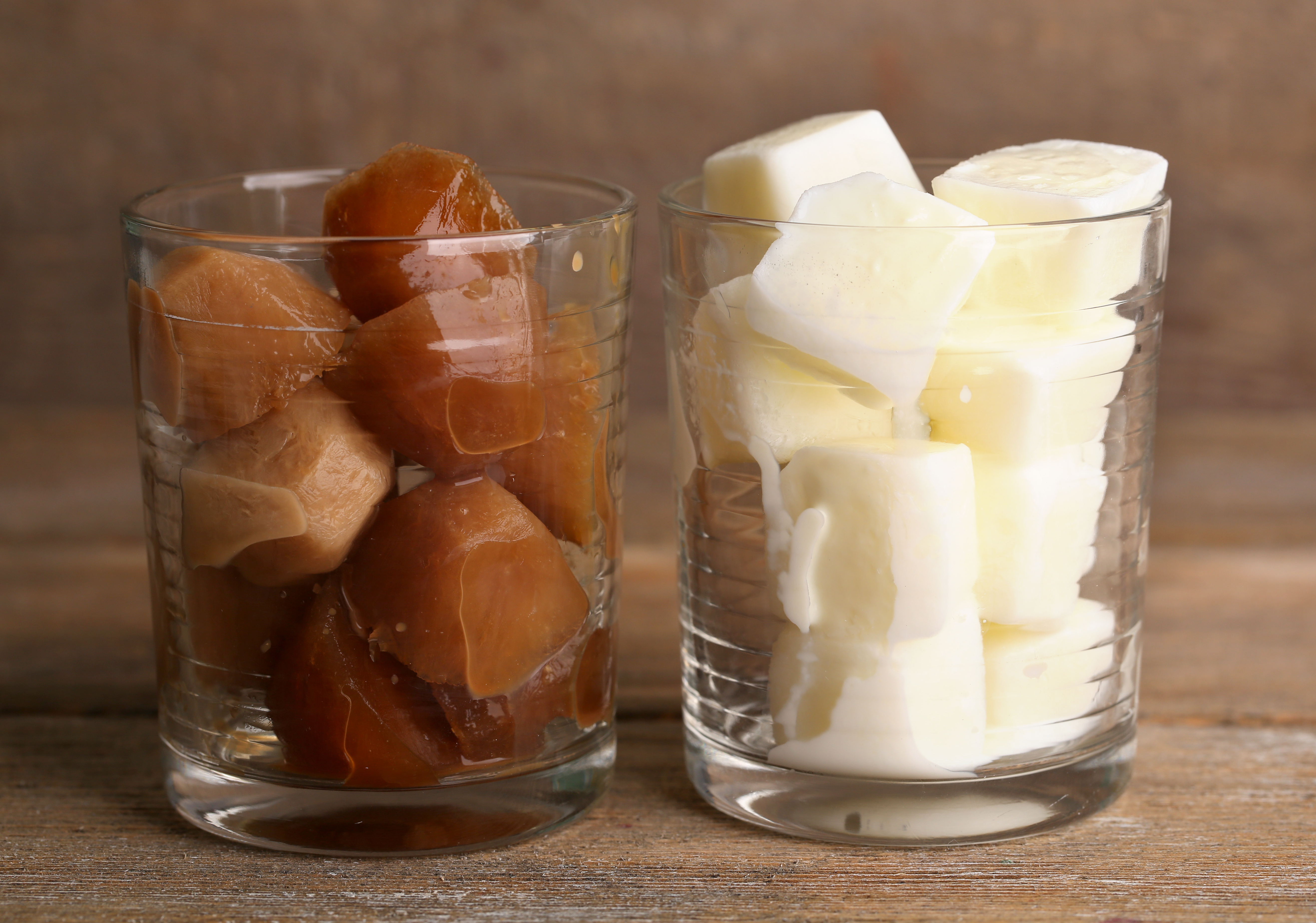 Iced coffee and milky cubes in glass on wooden background